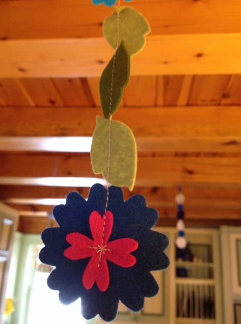 Up with the new (springy flower garland) and down with the old (blue and white snowflake garland).