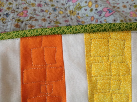 Stitches trace the edge of the quilt just inside the binding: perfect!
