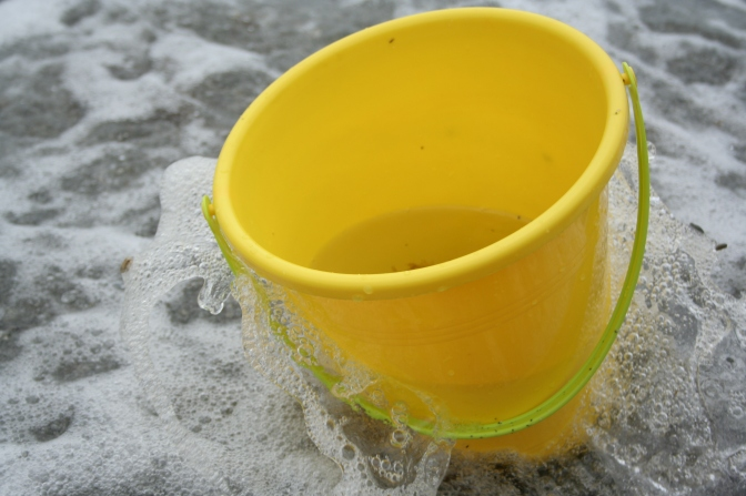 yellow bucket in the surf