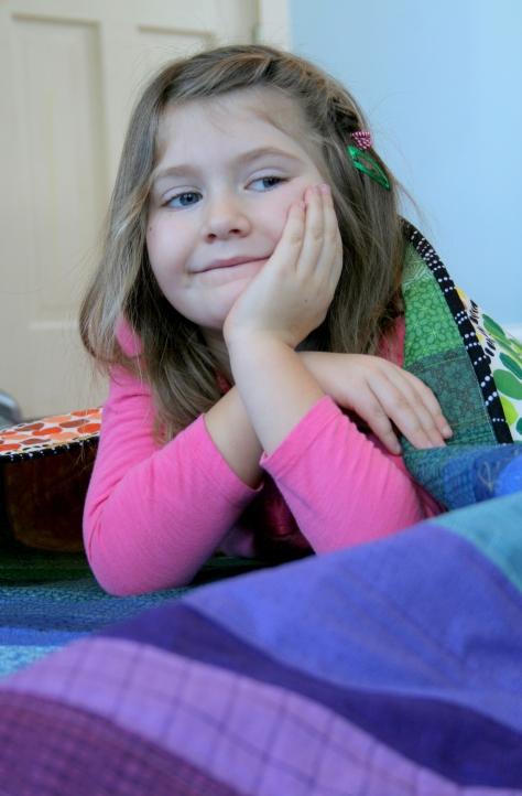 maddie on her rainbow quilt