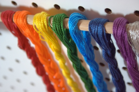 rainbow floss braids on wooden dowel