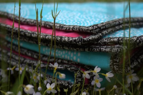 folded quilt in the rainy grass