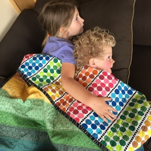 snuggling kiddos under rainbow quilt